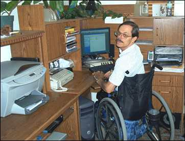Fred Adams working at the computer at his Mosquito home